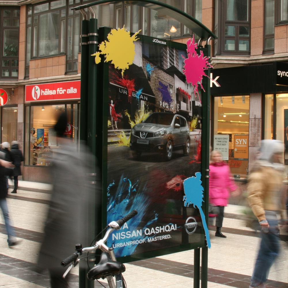 Trafikreklam med tryckta affischer på stan